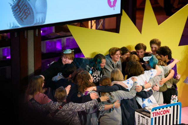Eine Gruppe junger Menschen umarmt sich auf einer Bühne