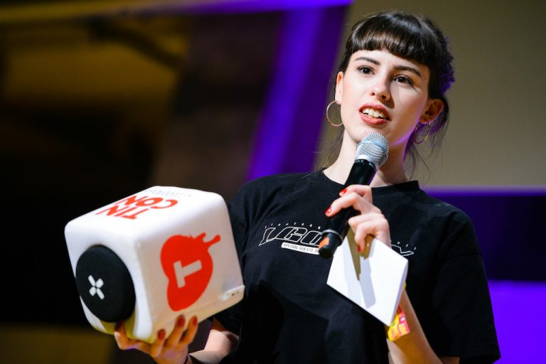 Eine junge Frau hält ein Mikrofon in der einen und ein Wurfmikrofon in der anderen Hand