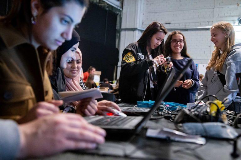 Mehrere junge Frauen sitzen an einem Tisch und schauen auf Notebooks