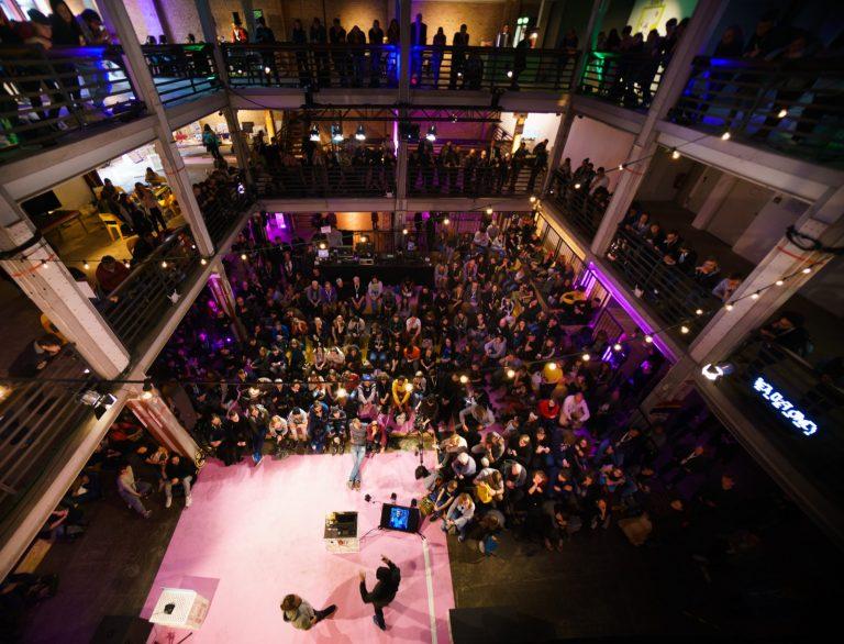 Eine größere Anzahl Menschen schaut auf eine Bühne