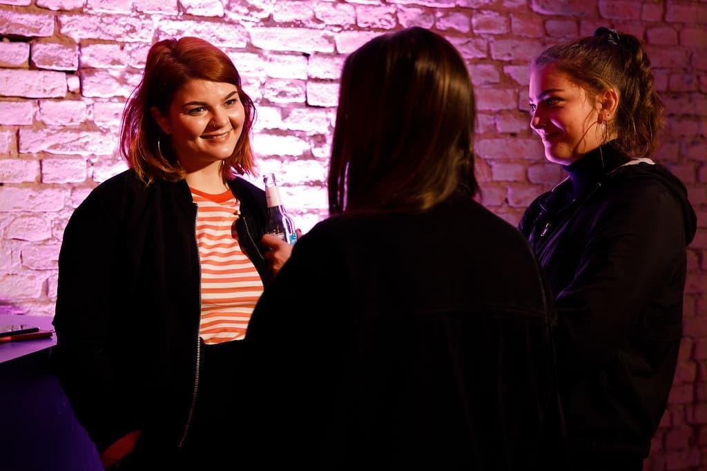 Drei Frauen stehen zusammen und unterhalten sich