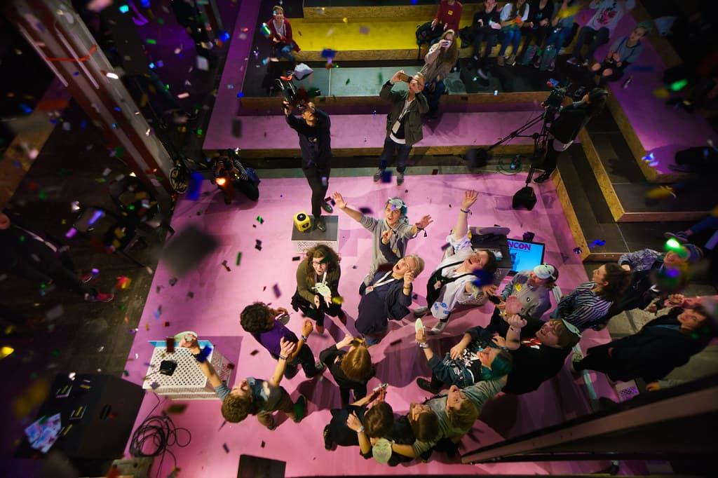 Eine Gruppe Menschen steht auf einer Bühne, auf die Konfetti regnet