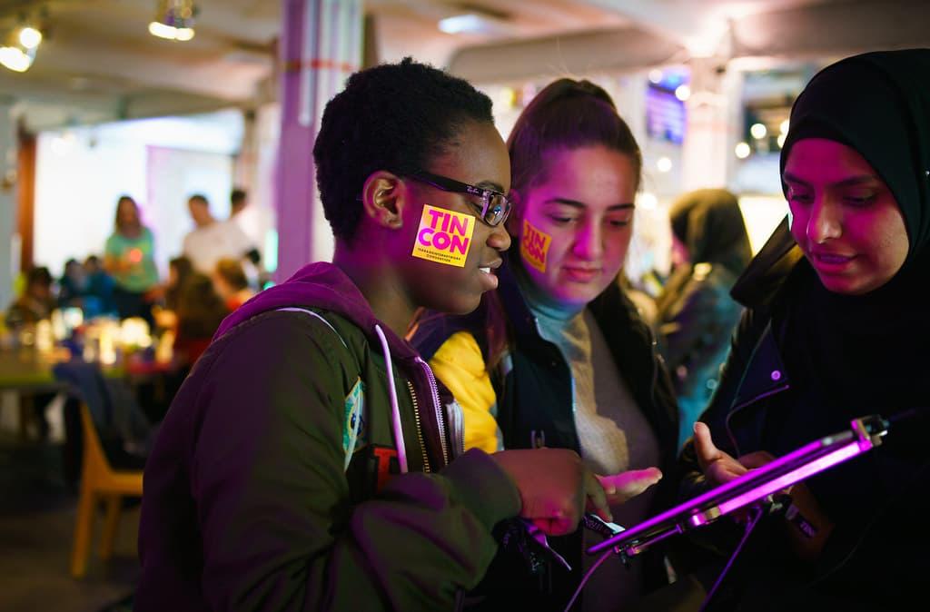 Drei junge Frauen schauen gemeinsam auf ein Tablet