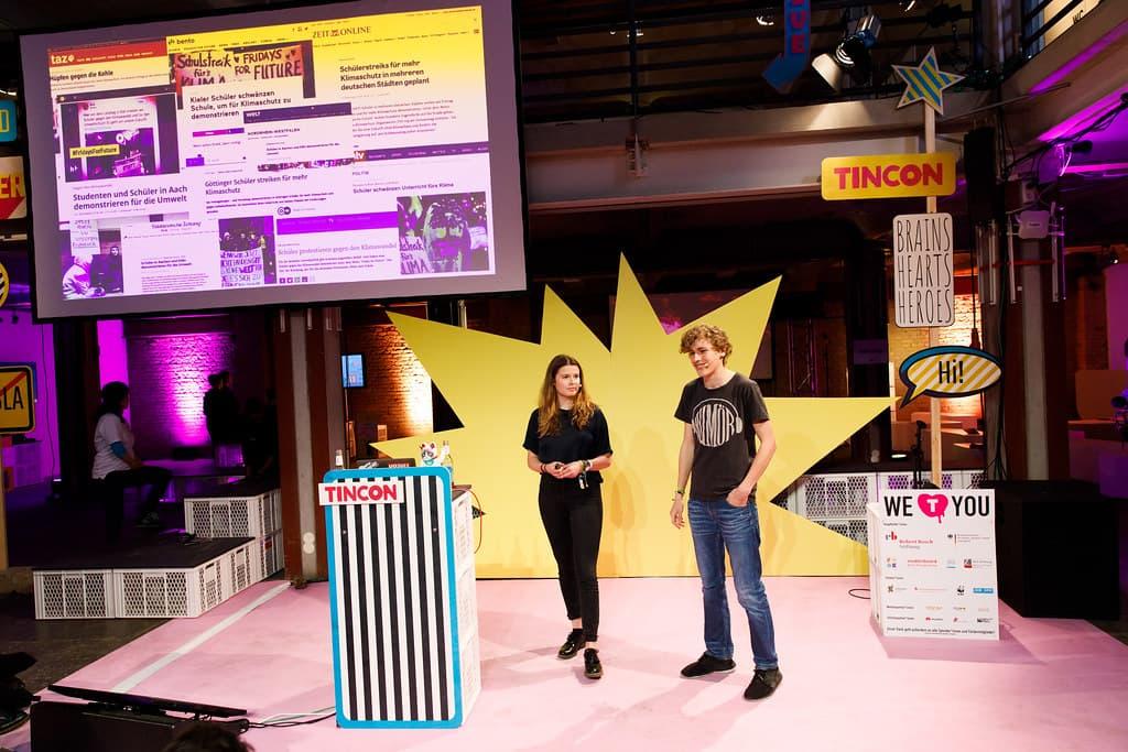 Eine junge Frau und ein junger Mann stehen auf einer Bühne