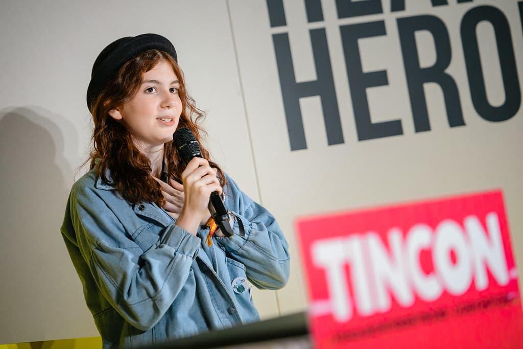 Eine junge Frau hält und spricht in ein Mikrofon